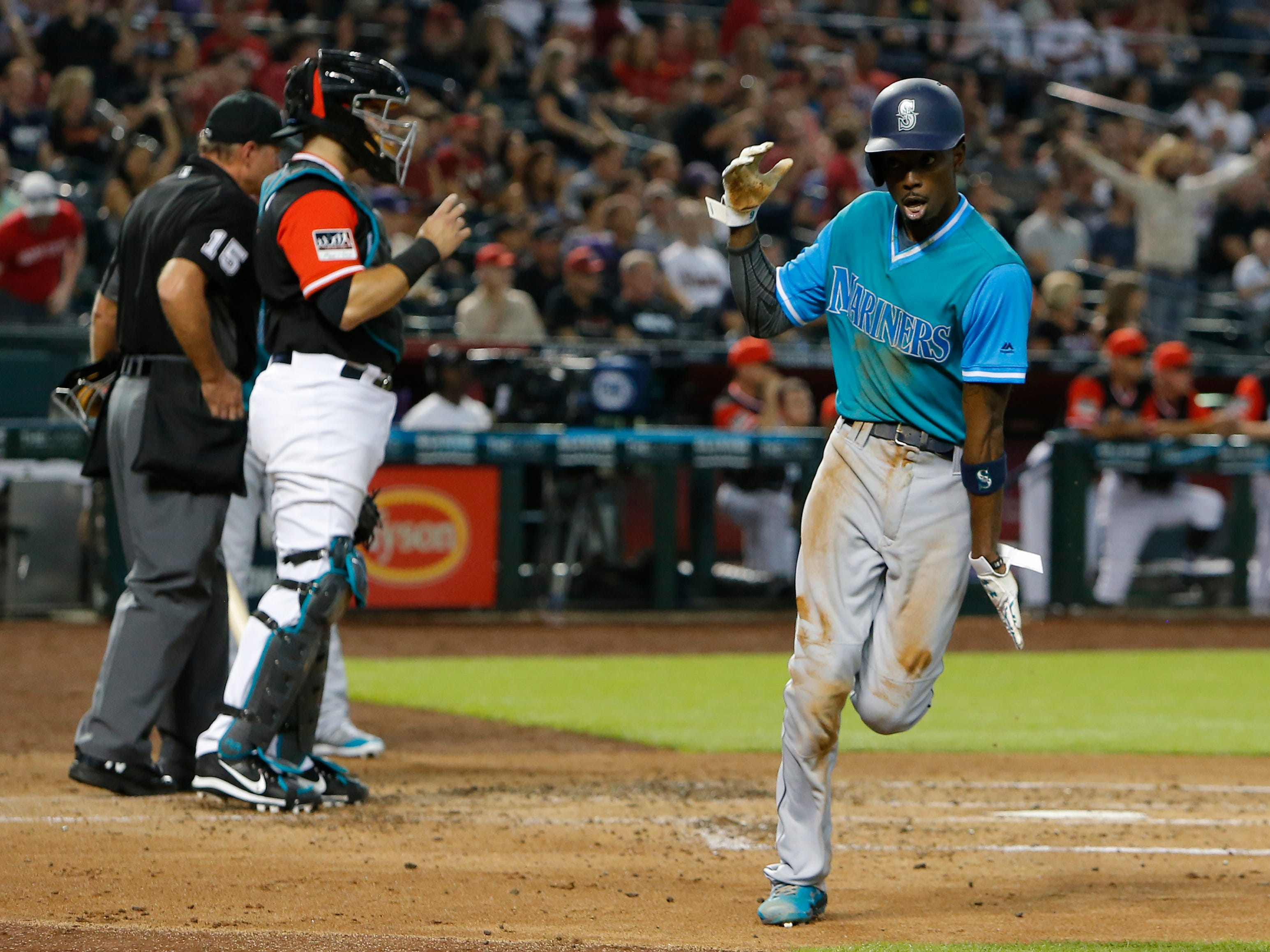 Seattle Mariners Dee Gordon celebrates after scoring on a throwing error by Arizona Diamondbacks pitcher Zack Godley after Gordon stole third base during the third inning of a baseball game Friday, Aug. 24, 2018, in Phoenix.