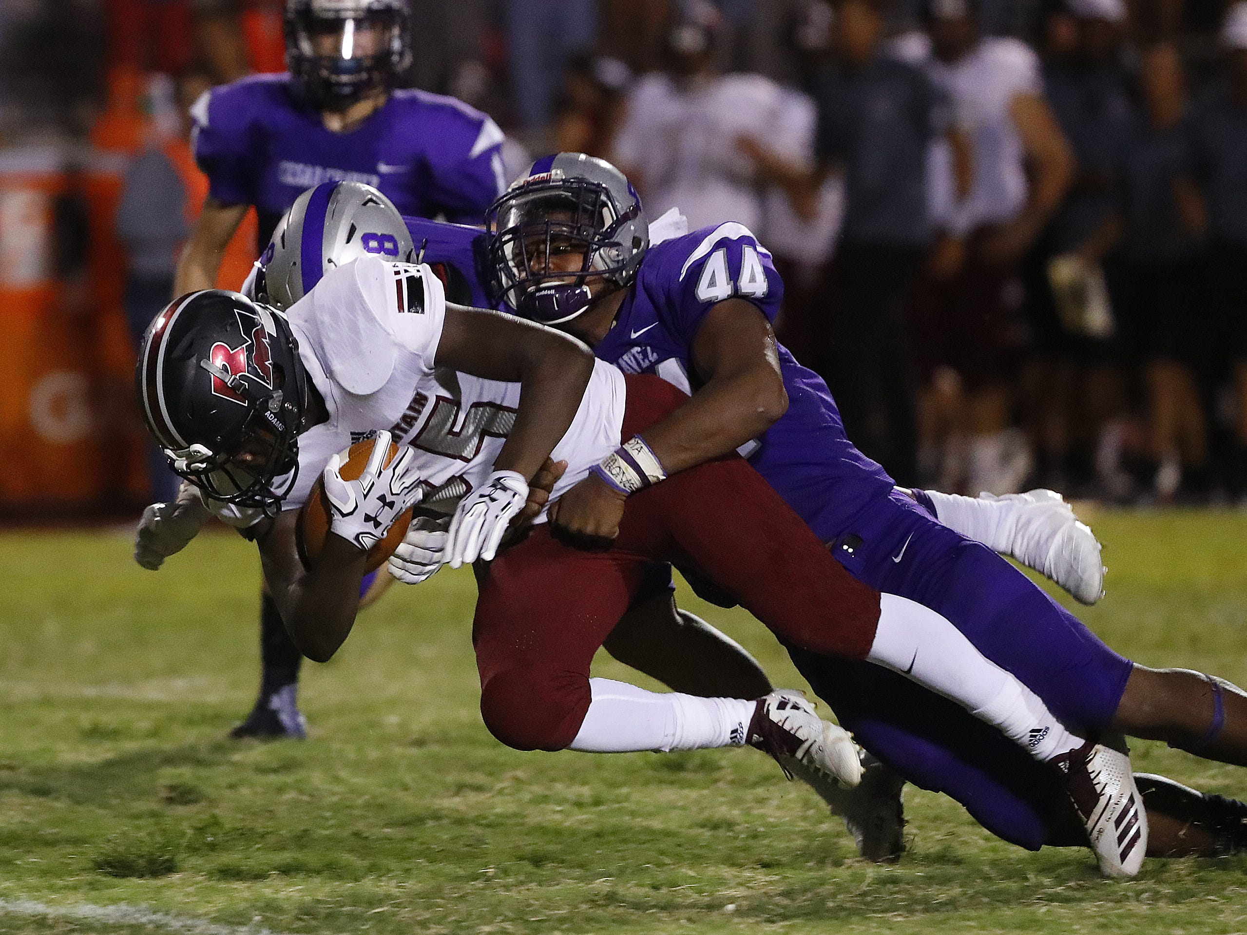 Cesar Chavez's Antwaun Winfield (44) tackles Red Mountain's Jarquell Garner (45) during a game at Cesar Chavez High School in Phoenix, Ariz. on Aug. 23, 2018. #azhsfb