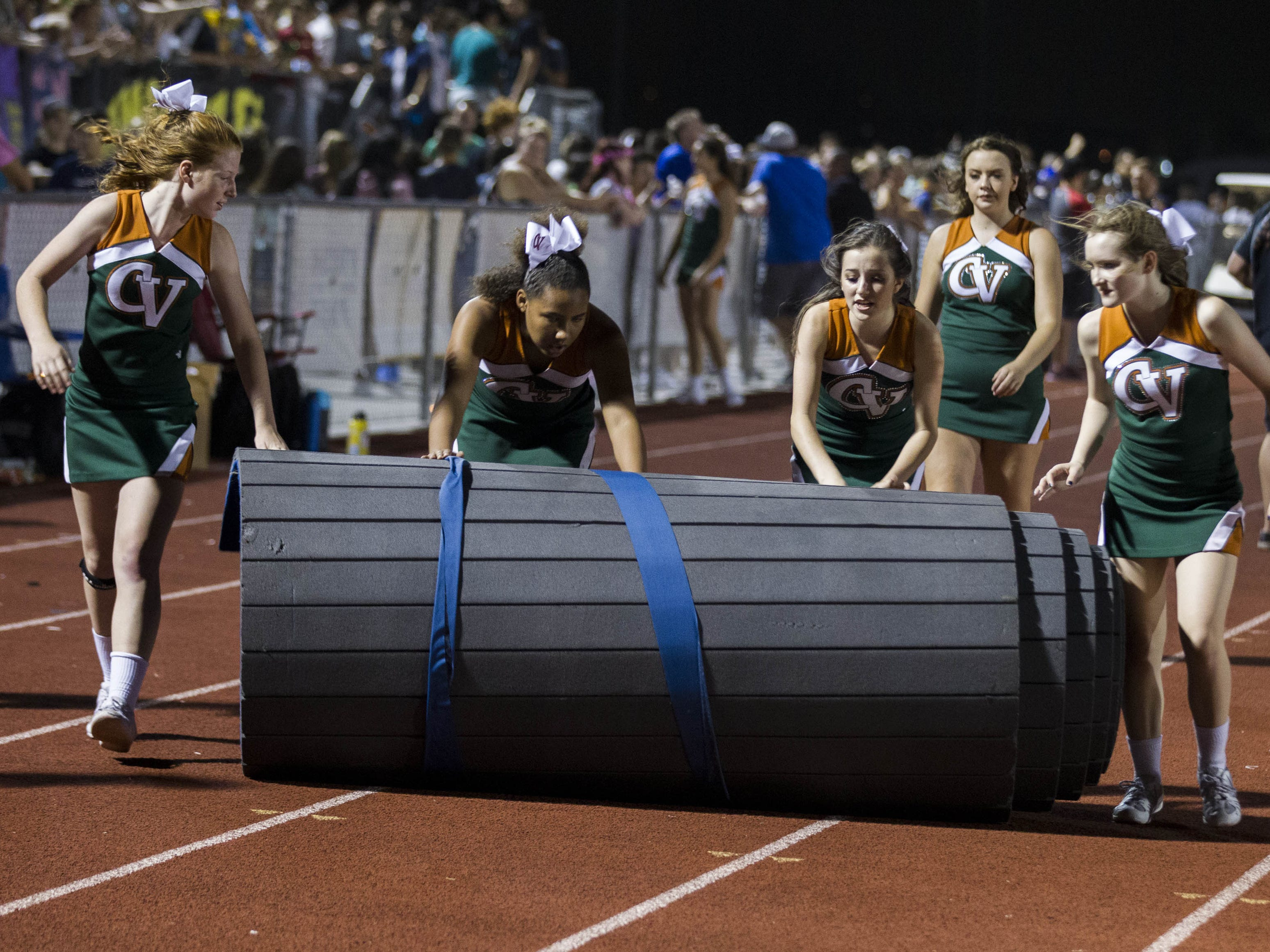 Campo Verde High cheerleaders roll up a mat during halftime after their game with Mesquite was in a weather delay in Gilbert Friday, Aug. 24, 2018. Campo Verde was up 22-7 at halftime. #azhsfb
