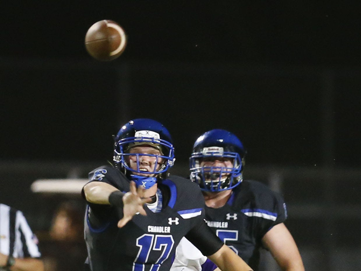 Chandler Jacob Conover (17) passes the ball while being tackled by Queen Creek Christian Fuhrman (54) during a high school football game at Chandler High on August 24, 2018. #azhsfb