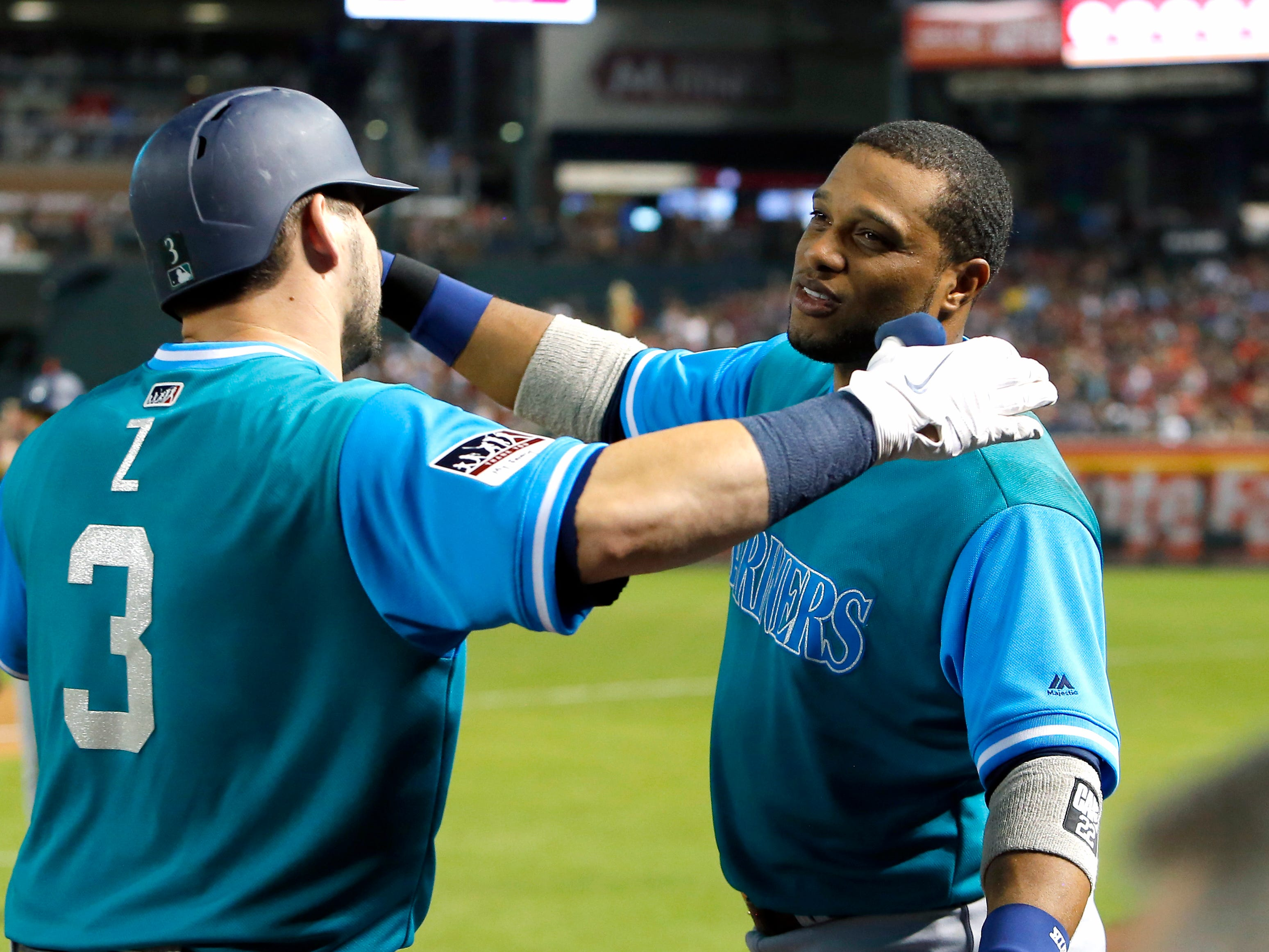 Seattle Mariners' Mike Zunino (3) clebrates with Robinson Cano after hitting a solo homerun against the Arizona Diamondbacks in the sixth inning during a baseball game, Friday, Aug. 24, 2018, in Phoenix.