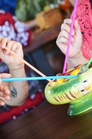 Patrons enjoy the shareable scorpion bowl cocktail at Hula's Modern Tiki.