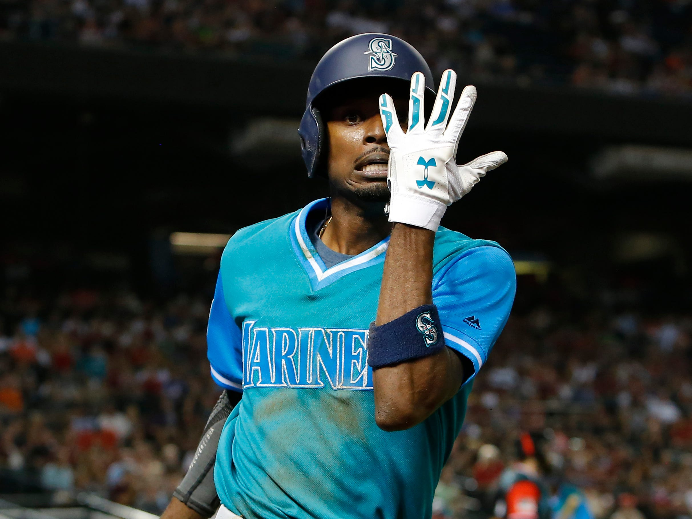 Seattle Mariners Dee Gordon celebrates after scoring on a throwing error by Arizona Diamondbacks pitcher Zack Godley after stealing thirdbase in the third inning during a baseball game, Friday, Aug. 24, 2018, in Phoenix.
