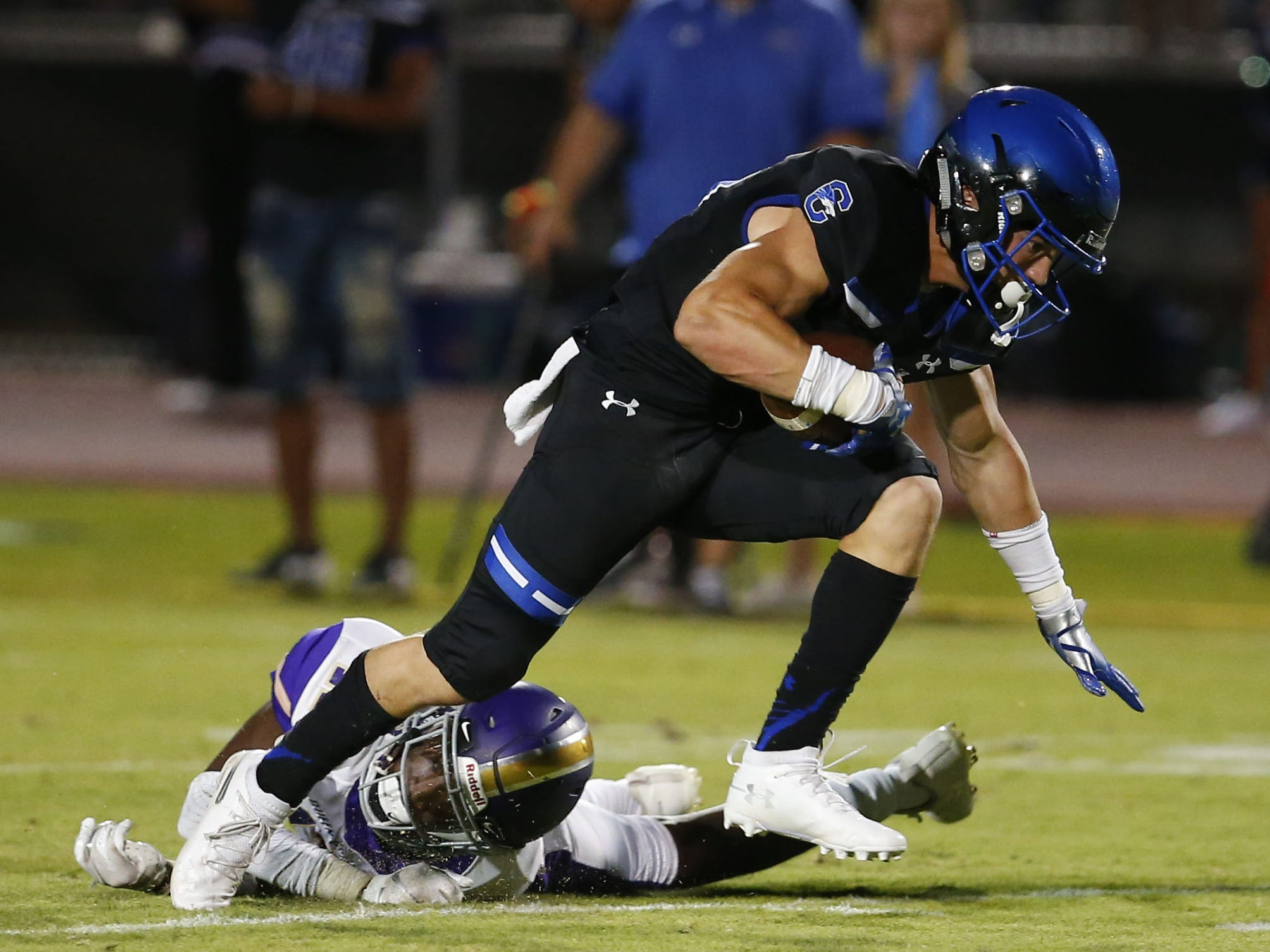 Chandler Gunner Maldanado (13) breaks a tackle by Queen Creek Dartanyon Sneed (11) during a high school football at Chandler High on August 24, 2018. #azhsfb