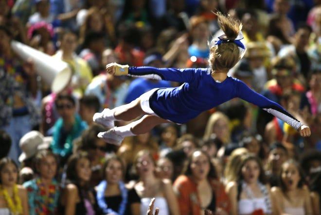 Chandler cheerleader performs a stunt during a high school football against Queen Creek at Chandler High on August 24, 2018. #azhsfb