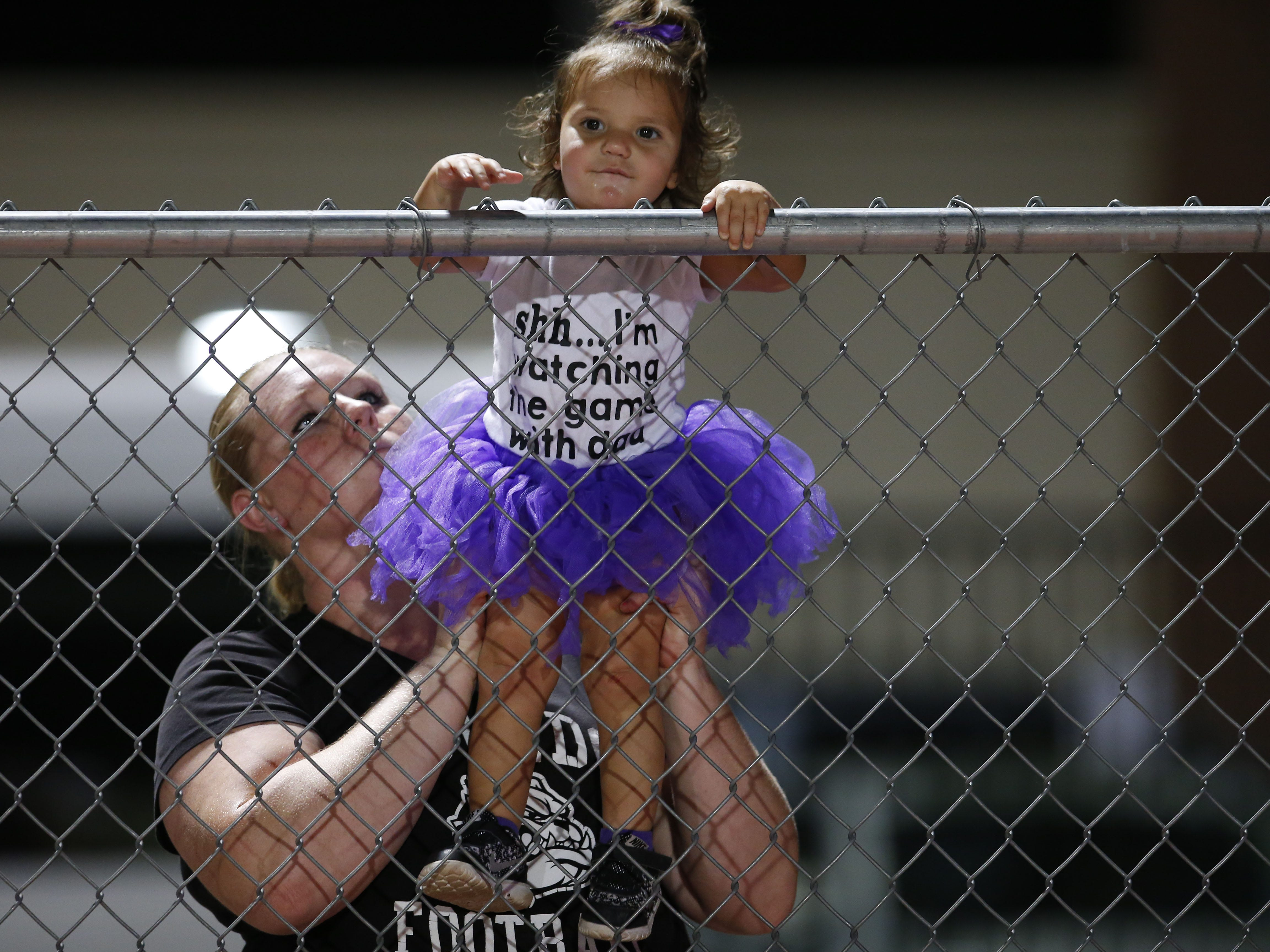 Amanda Dominguez and her daughter, Lily, 1, cheer for Queen Creek during a high school football against Chandler at Chandler High on August 24, 2018. #azhsfb