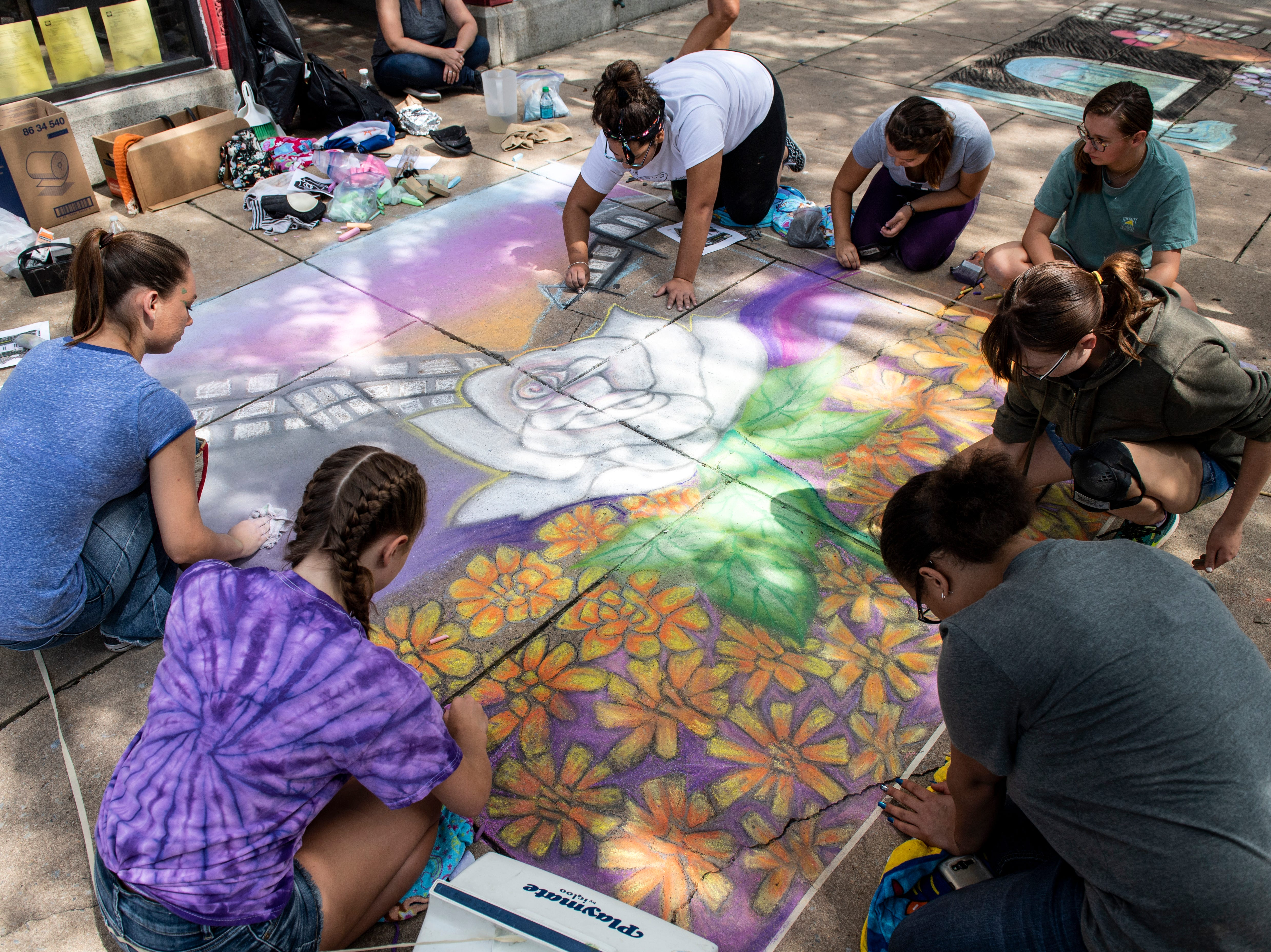Briana Allen, from left, Lilly Haugh, Alexis Trinidad, Abigail Waples, Katie Mummert, Savannah Weaver and Jen Vega, all Northeastern art students, part of the National Art Honor Society, work on a chalk walk piece for the competition, Saturday, Aug. 25, 2018. The art festival continues through Sunday, hosting over 100 artists along the Codorus Creek.