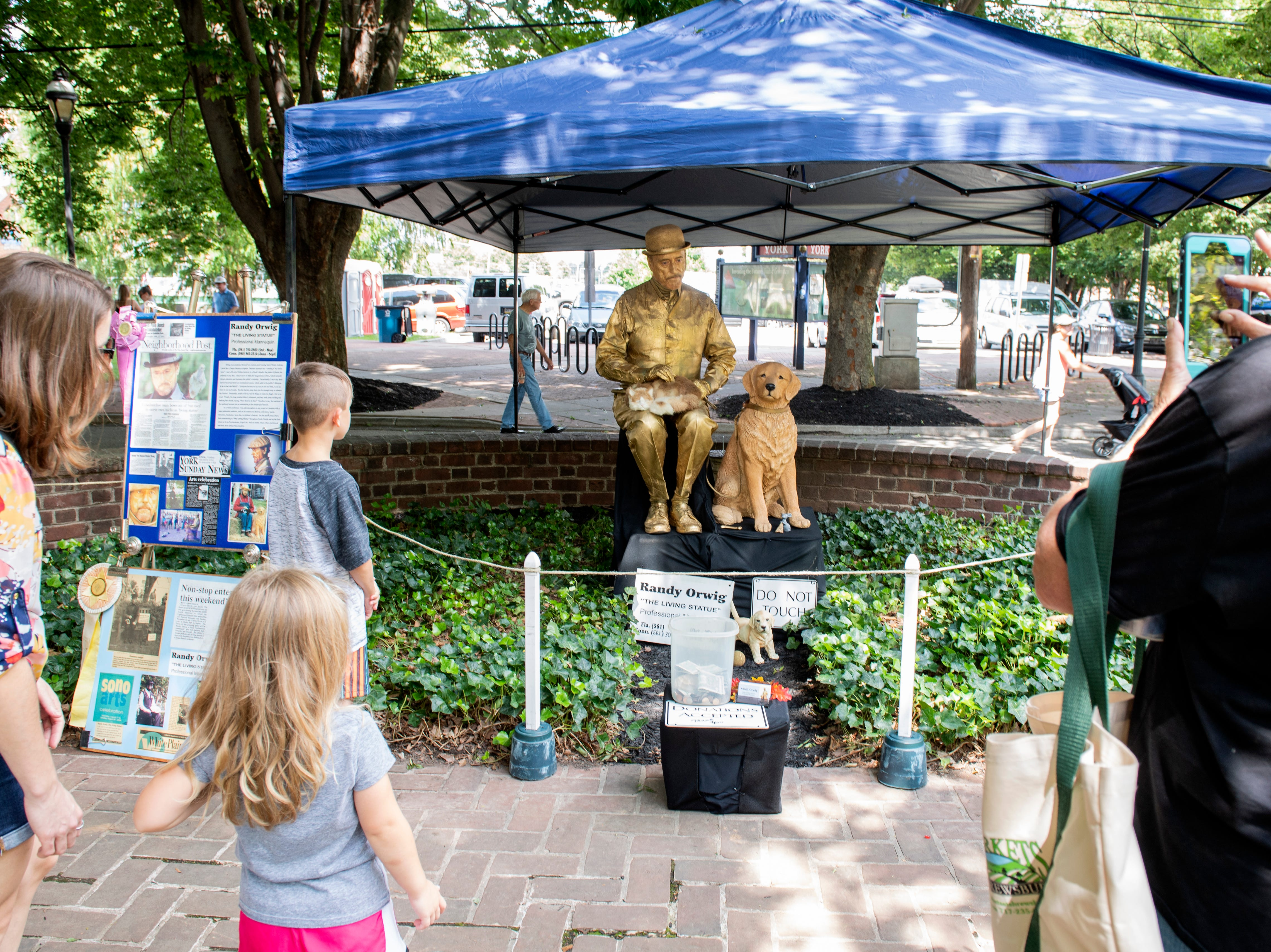 Randy Orwig, 'the living statue,' performs in front of passersby at Yorkfest, Saturday, Aug. 25, 2018. The art festival continues through Sunday, hosting over 100 artists along the Codorus Creek.