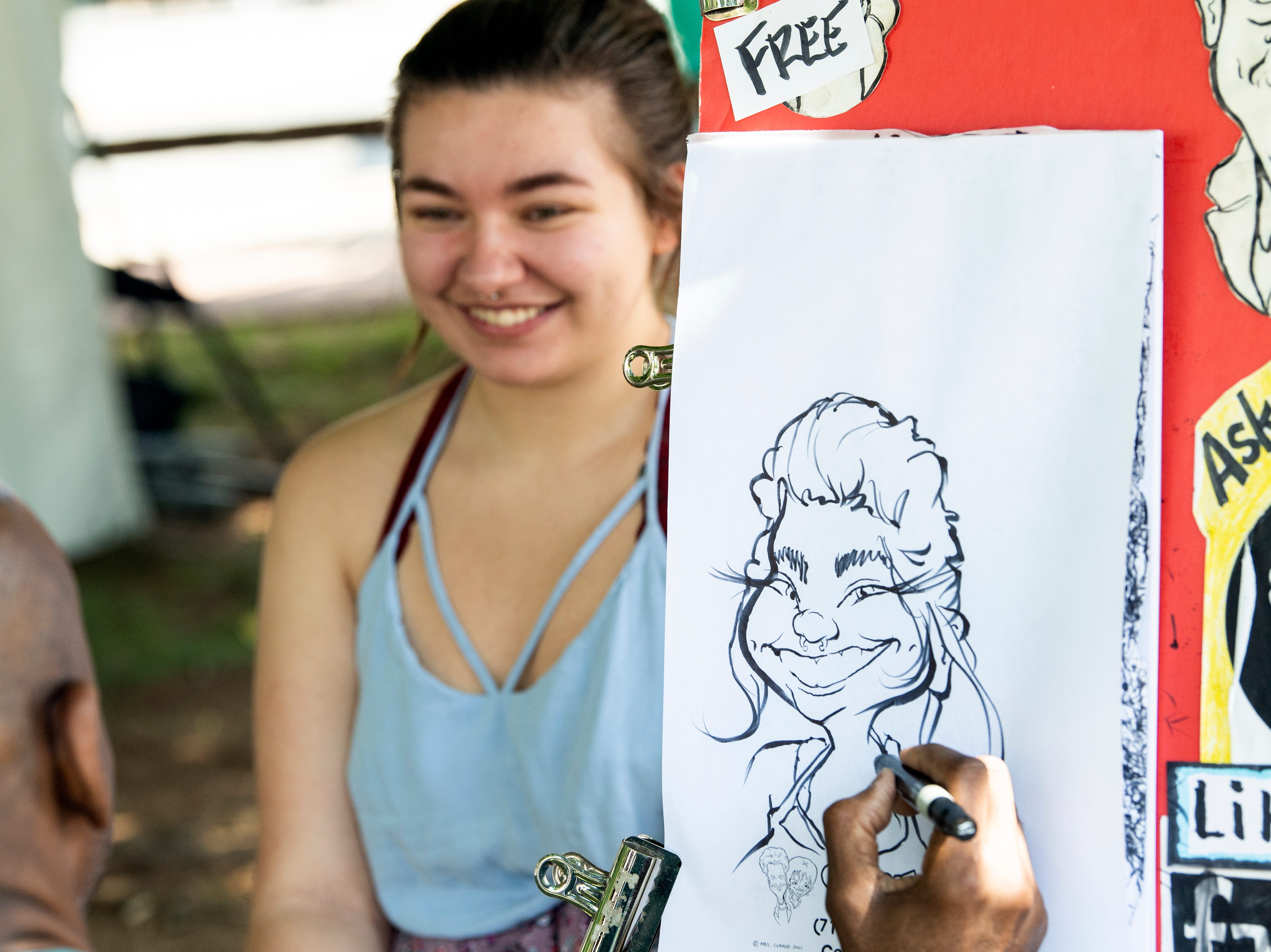 Daysha Brown sits for a free caricature by Mel Conrad at Yorkfest, Saturday, Aug. 25, 2018. The art festival continues through Sunday, hosting over 100 artists along the Codorus Creek.