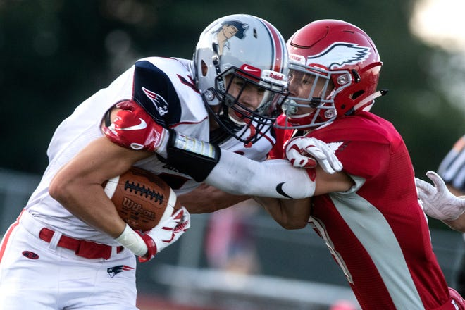 New Oxford's Connor Becker, left, runs for more yards as Bermudian's Chase McMillan goes for the tackle, Friday, Aug. 24, 2018. The Eagles skimmed past the Colonials, 28-22.