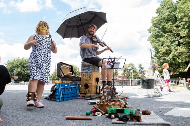 Brynlee Dietrich, 6, left, plays along with musician Ian Carroll during Yorkfest, Saturday, Aug. 25, 2018. The art festival continues through Sunday, hosting over 100 artists along the Codorus Creek.