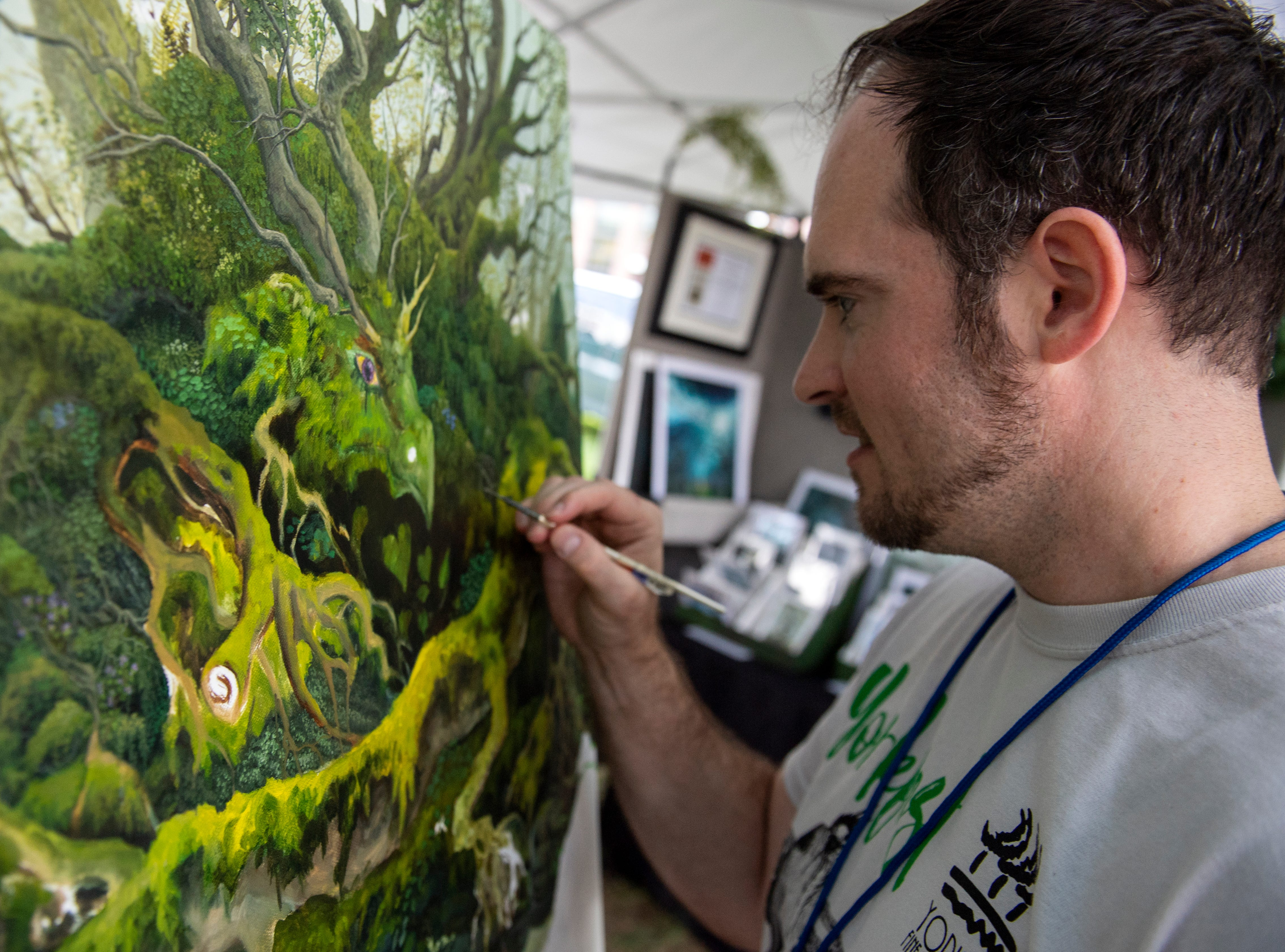 Jonathan Carrier, of Camp Hill, works on a painting outside his booth at Yorkfest, Saturday, Aug. 25, 2018. The art festival continues through Sunday, hosting over 100 artists along the Codorus Creek.