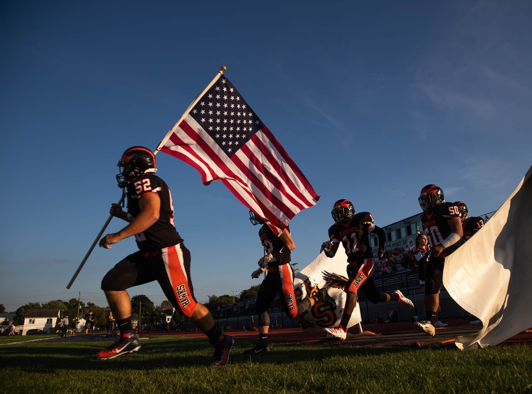 Hanover's Shane Warehime (52) holds an American flag as the Hanover Nighthawks enter the field for a football game between Hanover and Susquehannock, Friday, Aug. 24, 2018, at the Sheppard-Meyers field in Hanover.