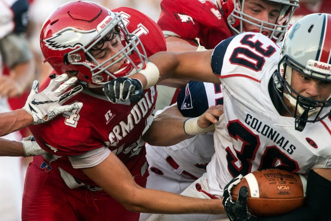Bermudian Springs' Tyler Sims (14) goes to tackle New Oxford's Haiden Milhimes (30), Friday, Aug. 24, 2018. The Eagles skimmed past the Colonials, 28-22.