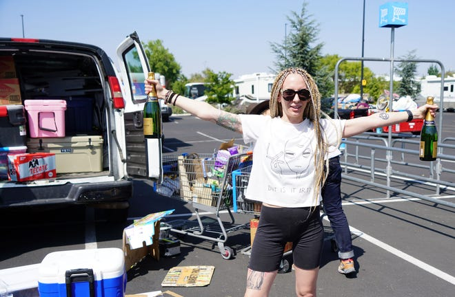 Burning Man participant Shelby King shows off a bottles during a break from packing a rental van after buying supplies at a Reno, Nevada, Walmart.