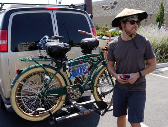 Software engineer Alan Derk of Venice, California checks out a passing vehicle in a Walmart parking lot after attaching his van's license plate to the bikes attached to the back, hoping to forestall a traffic stop conducted by police who appear to be targeting Burning Man participants driving to the 2018 event.