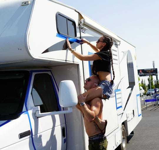 Patricia Adamssom sits atop the shoulders of Robin Schyllert as she tapes up cracks around the windows of the RV the two have rented for Burning Man. Dust from the desert plain where the event takes place is hard to remove and taping up windows is a time-honored way of keeping the dust from inside vehicles.