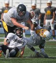 Irondequoit wide receiver Kyle Taylor, right, looses his handle on a reception as he gets hit by a pair of McQuaid defenders during their scrimmage Saturday, Aug. 25, 2018, at Irondequoit High School.