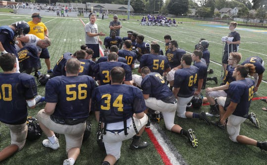 Spencerport head coach John Dowd talks to his huddled up players following their scrimmage against East.