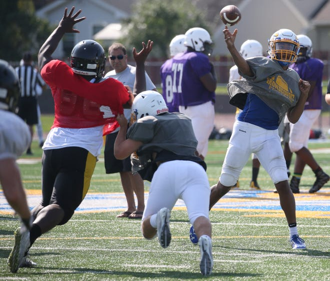 Irondequoit quarterback Freddy June gets the pass off ahead of the pressure from McQuaid's Aldrin Wilson, left, during their scrimmage Saturday, Aug. 25, 2018, at Irondequoit High School.  Irondequoit hosted the four team scrimmage, that also included East High and Spencerport.