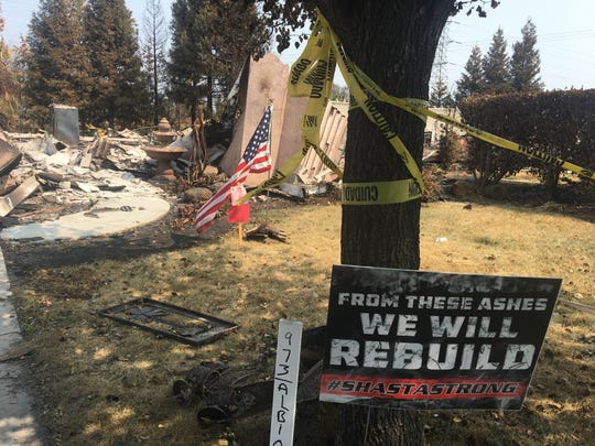 "Tim Strohmayer of Redding, lost his home in the Carr Fire.  A sign that says ""FROM THESE ASHES WE WILL REBUILD"" sits in his yard. He plans to rebuild."