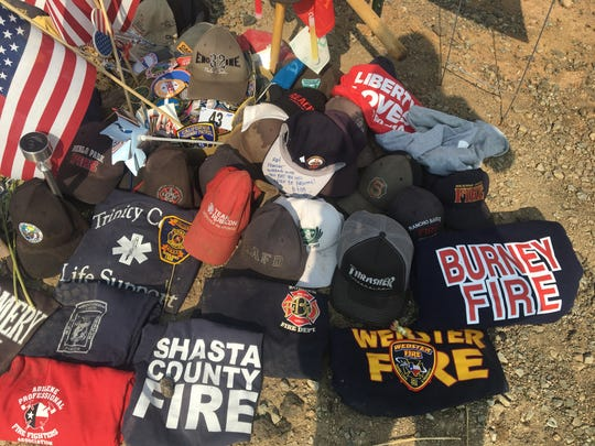 Numerous firefighter caps and T-shirts make up the roadside memorial for Redding fire prevention inspector Jeremy Stoke.