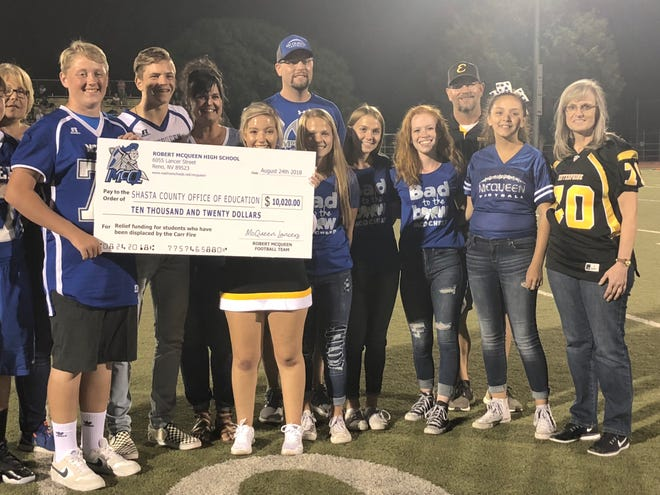 Representatives from McQueen High School present Shasta County superintendent of schools Judy Flores with a $10,020 check to help those affected by the Carr Fire.