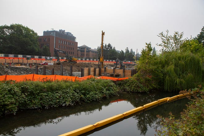 In this Monday, Aug. 20, 2018 photo, the construction site for the new $1 billion Knight Campus for Accelerating Scientific Impact overlooks the Mill Race in Eugene, Ore. The University of Oregon is planning to rework this section of the Mill Race. The work will include dredging sediment out of the river, building a boardwalk, building new bridges, and cleaning nearby stormwater runoff.