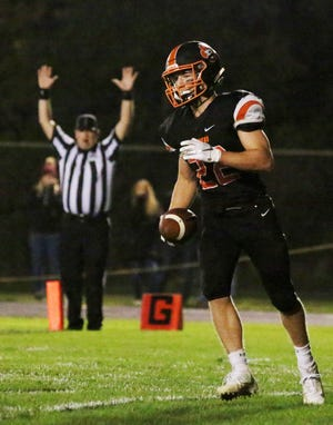 Plymouth's Josh Koll (22) holds the ball after scoring a touchdown against Sheboygan Falls on Friday.