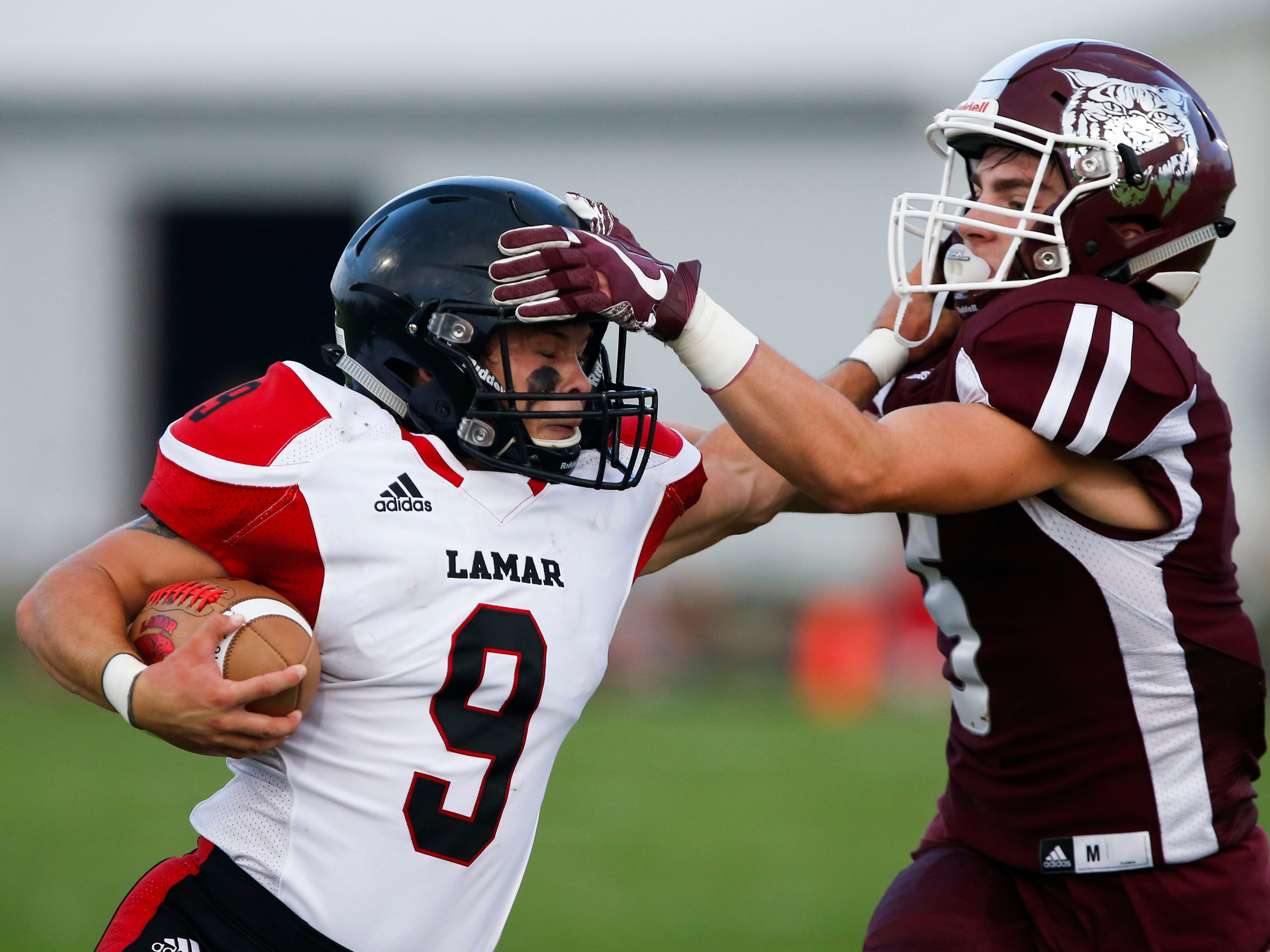 Lamar High School senior Trevor Medlin carries the ball while attempting to deflect a tackle from Logan-Rogersville junior Mckinley Feith during a game at Logan-Rogersville on Friday, Aug. 24, 2018.