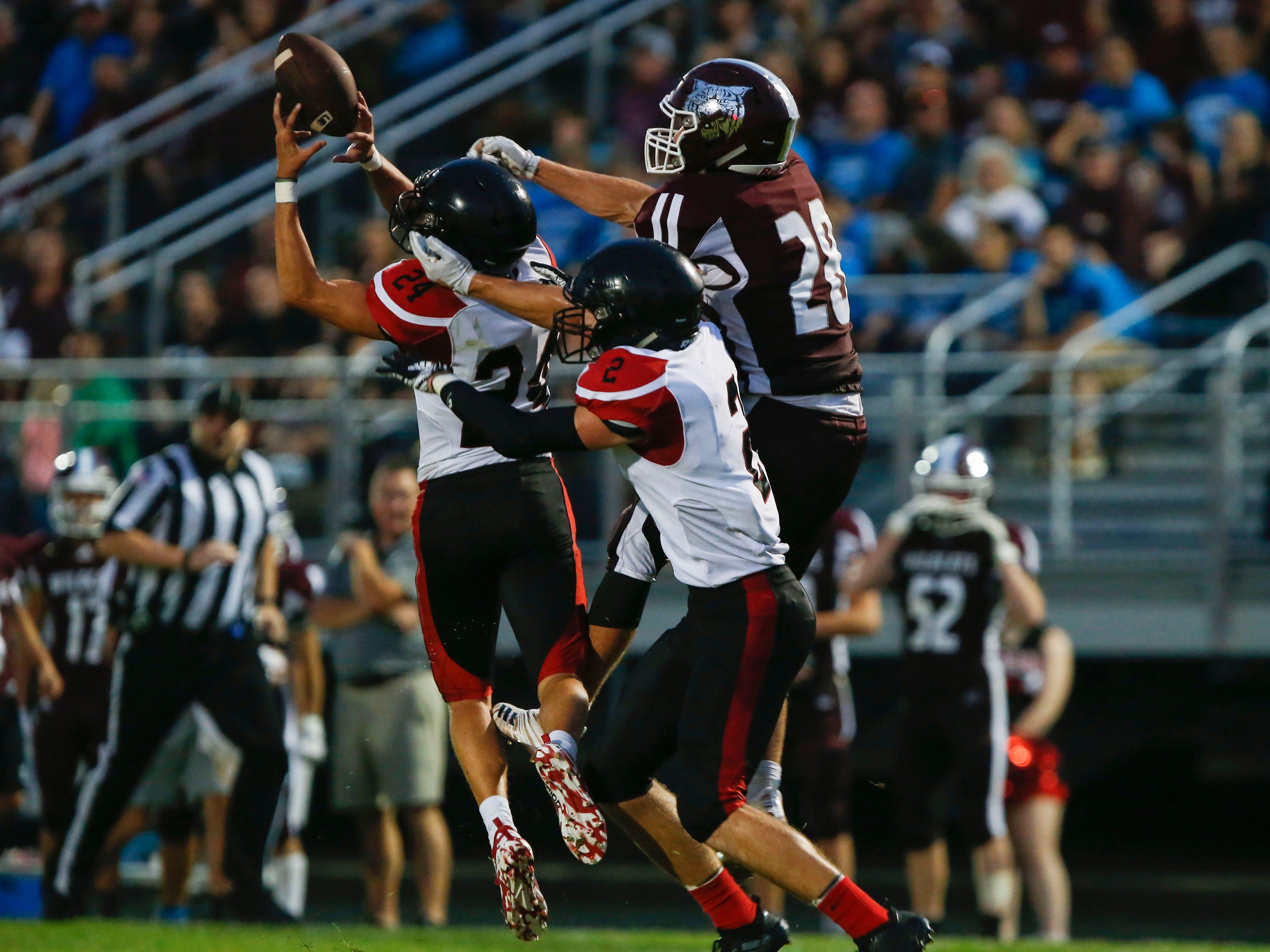 Lamar High School senior Landon Hardman makes an interception while Logan-Rogersville senior Ryker Strong attempts to break up the play during a game on Friday, Aug. 24, 2018.