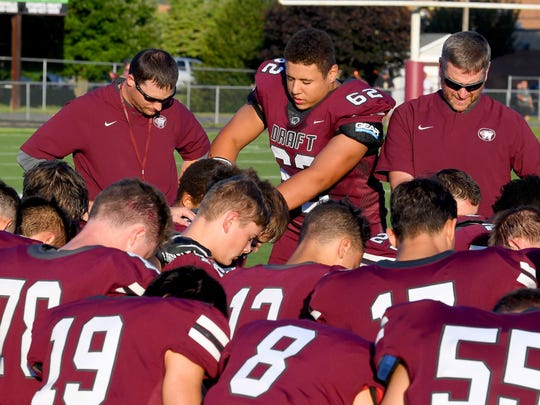 Stuarts Draft''s Justin Brown joins the rest of the team in a prayer before the start of their game against Waynesboro, played in Stuarts Draft on Friday, August 24, 2018.