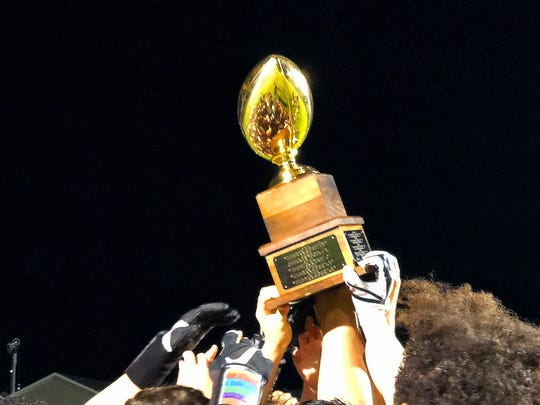 Stuarts Draft players hoist high and claim the game trophy for the year after defeating Waynesboro in a football game played in Stuarts Draft on Friday, August 24, 2018.