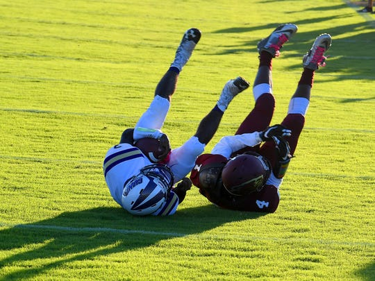 Waynesboro's Dayvon Young still has the ball as he rolls over with legs high next to Stuarts Draft's Jo'-el Howard who brought him down during a football game played in Stuarts Draft on Friday, August 24, 2018.