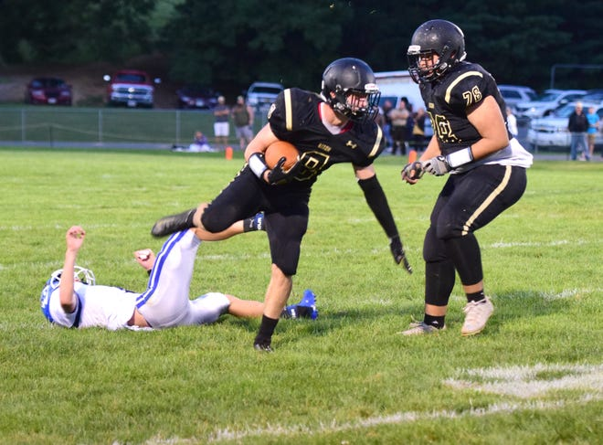 Buffalo Gap's Carter Rivenburg keeps his feet after leaping over a Fort Defiance defender during their season-opening game on Friday, Aug. 24, 2018, at Buffalo Gap High School in Swoope, Va.
