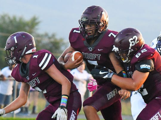 Stuarts Draft's Freddie Watkins runs the football as teammates Dustyn Fitzgerald and Justin Brown clear the way for him during a football game played in Stuarts Draft on Friday, August 24, 2018.