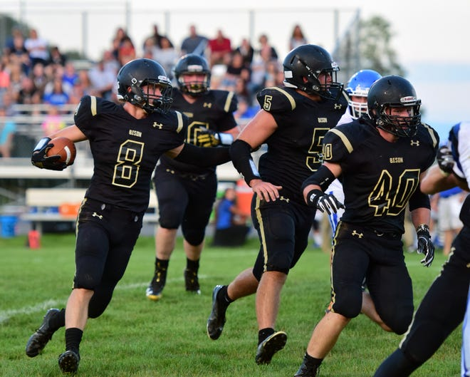 Buffalo Gap's Carter Rivenburg, left, follows teammates Seth Fitzgerald, center, and Ryan Wilcher, right, during the first half of the Bison's season-opening game against Fort Defiance on Friday, Aug. 24, 2018, at Buffalo Gap High School in Swoope, Va. Rivenburg scored on a 53-yard touchdown run on the play.