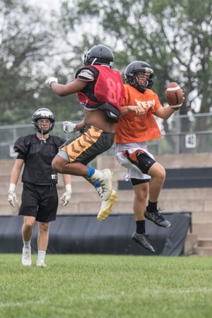 Quarterback Nate Trewick celebrates being on the receiving end of a long pass from fellow senior Isaiah Green during practice Thursday, Aug. 23, at Tech High School in St. Cloud.