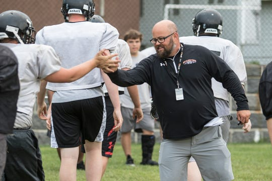 New Tech head coach Jon Benson gives an enthusiastic congratulations to his lineman for a job well done during practice Thursday, Aug. 23, at Tech High School in St. Cloud.