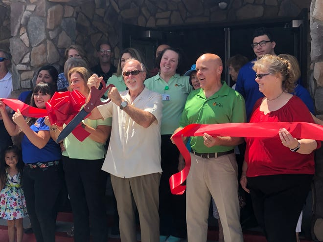Mayor Al Litman cuts the ribbon to signify the official opening of the second BeeHive Homes assisted living facility in Mesquite.