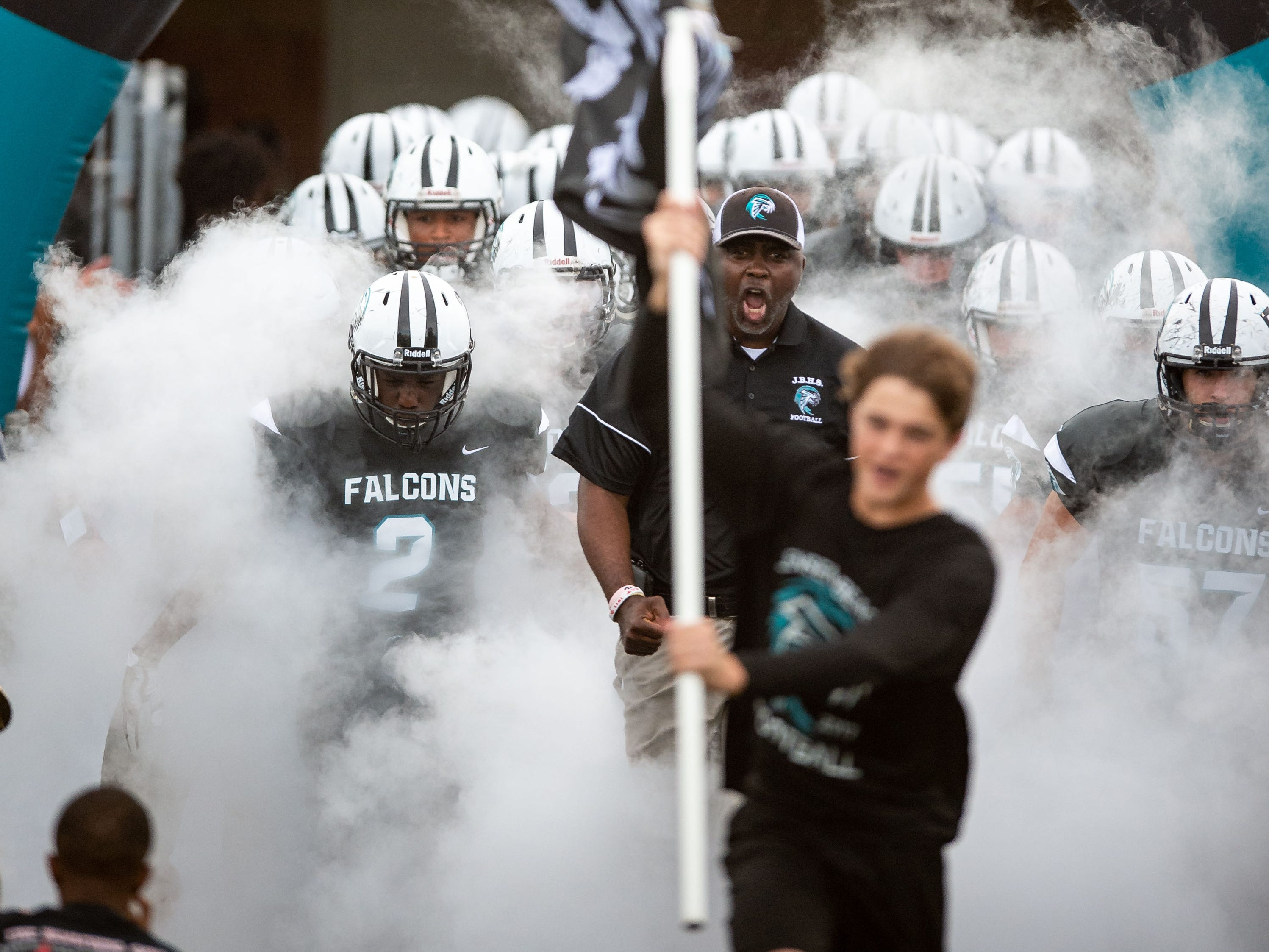 Jensen Beach head coach Tim Caffey leads his players onto the field to play South Fork during the high school football game Friday, Aug. 24, 2018, at Jensen Beach High School.