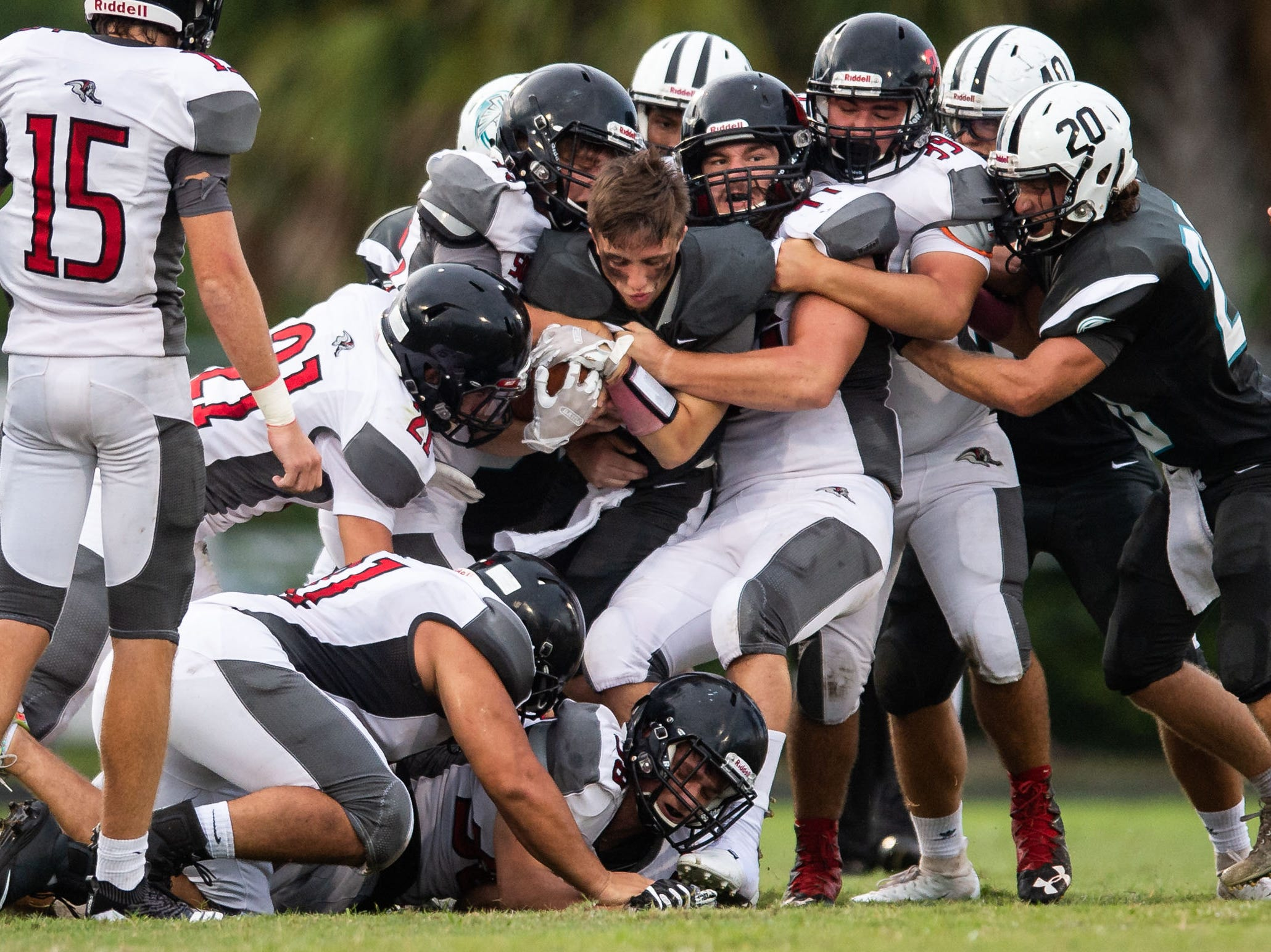 Jensen Beach's Bradyn Bytheway loses his helmet as is brought down by a gang of South Fork defenders, including Camp Gobler (center), during the first half of the high school football game Friday, Aug. 24, 2018, at Jensen Beach High School.