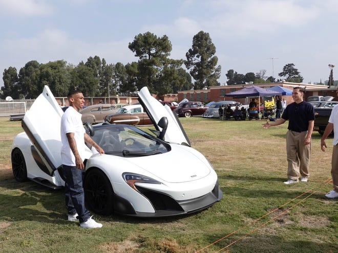 Jamarius Cole, left, poses with a gullwing McLaren on Saturday as Wyatt Warnars looks on. The McLaren and about 30 classic cars rolled into the Ventura Youth Correctional Facility for a special event, the first of its kind at the locked site.