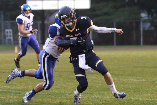 Wausau West quarterback Mitch Zahuroness, right, attempts to shake off Oshkosh West's Curtis Yokom during a Valley Football Association football game Friday at Thom Field.