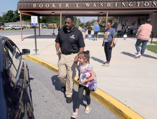 Barry Gaines, constable for the Capital School District, walks a kindergarten student to her waiting parent's car.