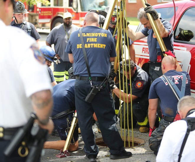 """Wilmington Fire Department firefighters work to rescue a person from a sewer under an alley behind the William """"Hicks"""" Anderson Community Center near West Fifth and Madison streets on Saturday afternoon."""