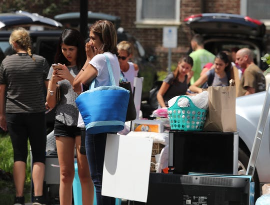 People and piles take up space outside the South Academy Street residence as 4,100 freshmen move into the University of Delaware in Newark in staggered waves during the school's move-in day for first-year students Saturday.