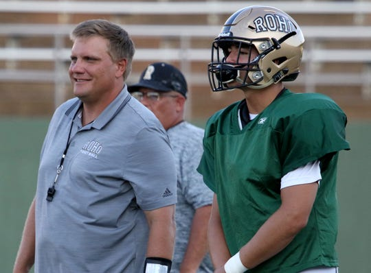 Rider head coach Marc Bindel and his quarterback Jacob Rodriguez  watch the second team offense play against Decatur in a scrimmage Friday, Aug. 24, 2018, at Memorial Stadium.