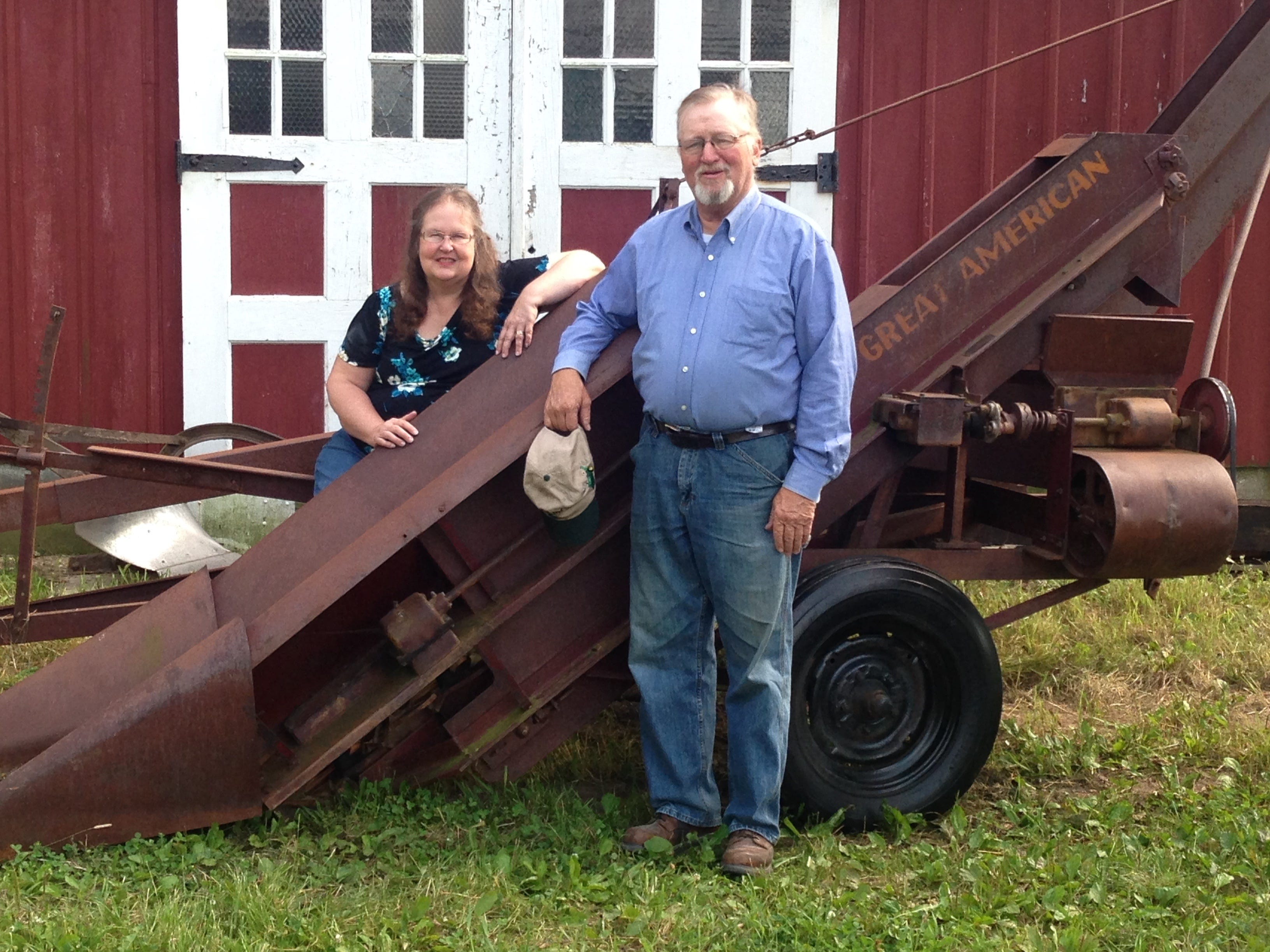 Phyllis and Bob Johnson, of rural Sycamore, Ill. stand by one of Bob's 25 corn pickers in his collection.