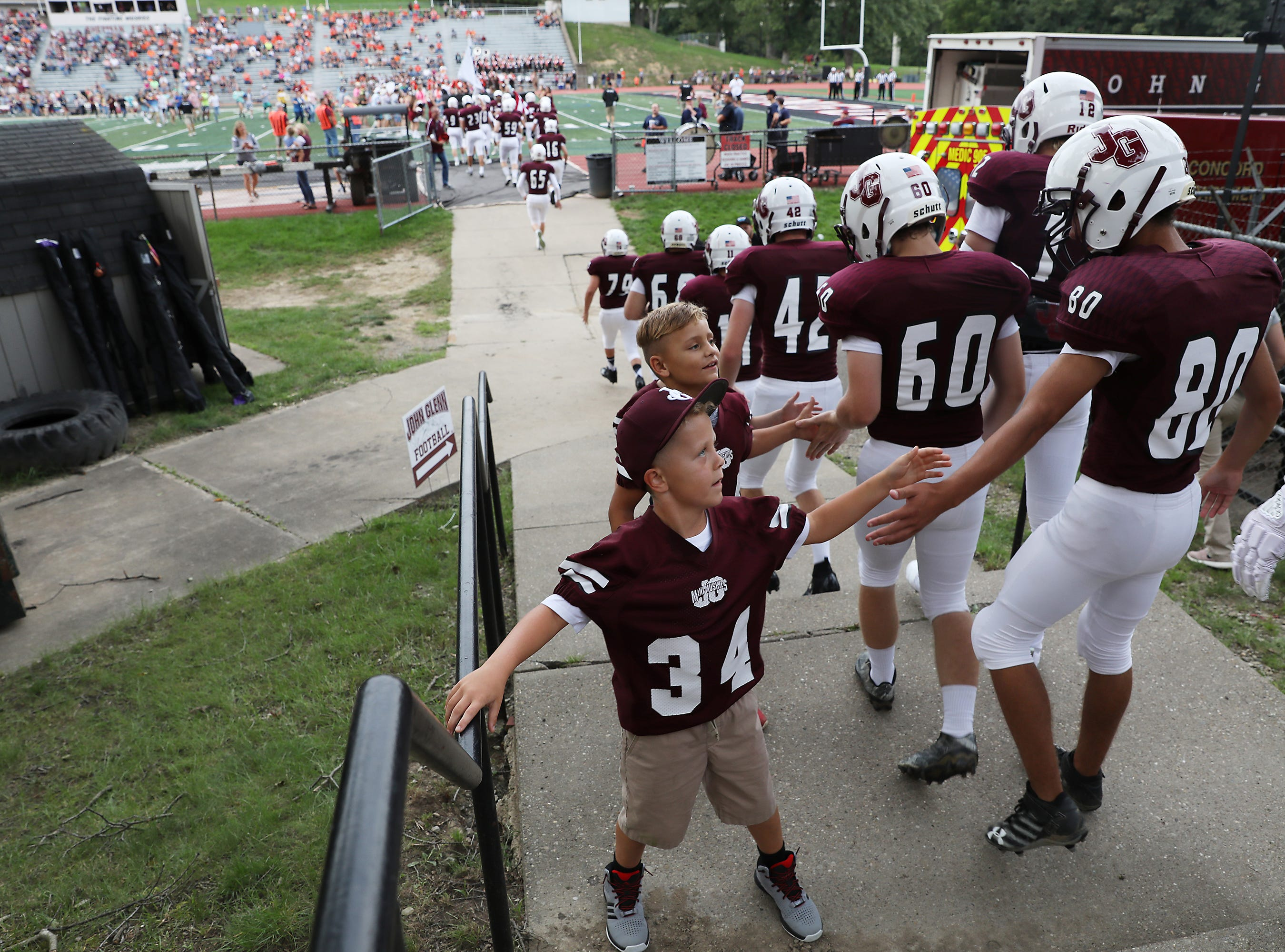 Youngsters seek high fives from John Glenn as the Muskies head to the field to take on Meadowbrook.